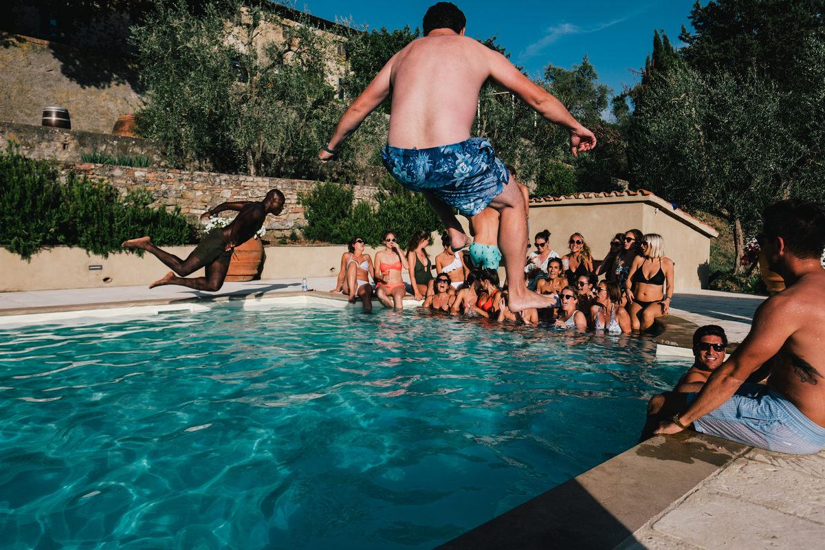 duik in het zwembad tijdens huwelijksfeest in Toscane Italië.